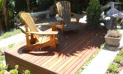 Garden design in Hout Bay, Cape Town. Wooden decking in balau timber surrounded by gravel and paved pathways. Finished off with indigenous colourful plants.